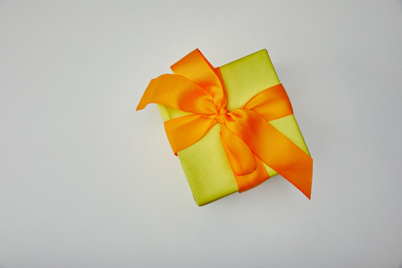 Bovenaanzicht van ingepakt cadeau met oranje strik geïsoleerd op een grijze achtergrond