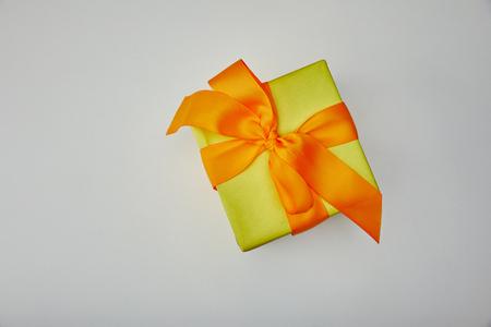 Vista dall'alto del regalo incartato con fiocco arancione isolato su sfondo grigio