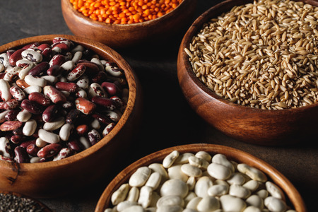 variety of beans in wooden bowls with oat groats on table Zdjęcie Seryjne - 116388683