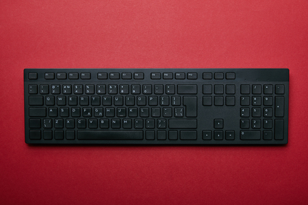 Top view of black plastic computer keyboard on red background