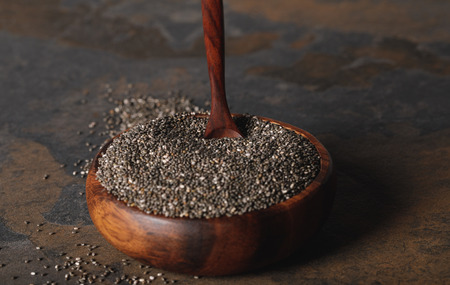 chia seeds with spoon in wooden bowl on table