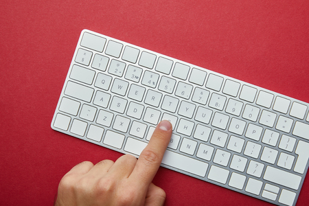 Cropped view of man pushing button on white computer keyboard on red background
