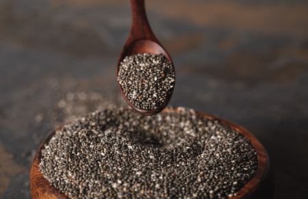 selective focus of wooden spoon and chia seeds in bowl Imagens