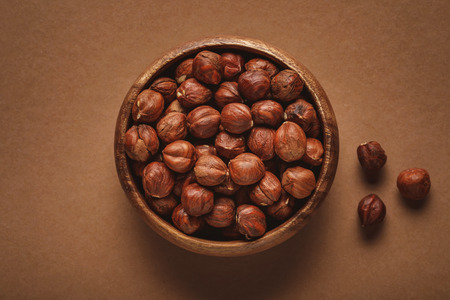 top view of in wooden bowl on shelled chestnuts brown background Archivio Fotografico