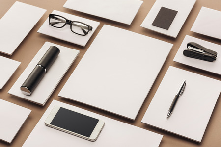 Empty sheets of paper, case, glasses, smartphone, pen and stapler on beige background 写真素材