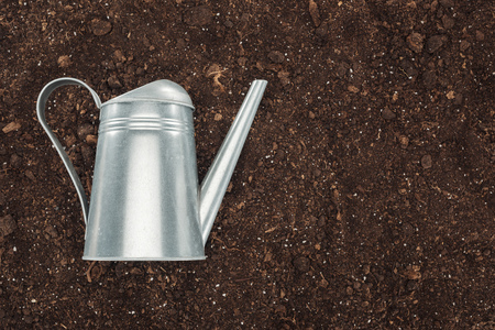top view of watering can on ground, protecting nature concept