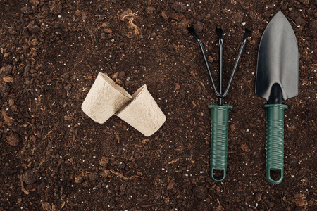 top view of used paper cups near rake and shovel on ground, protecting nature concept