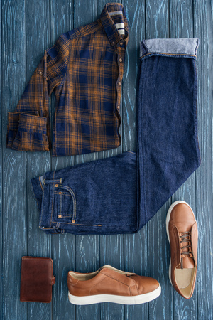 Flat lay with checkered shirt, denim pants and boots on wooden background