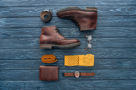 Flat lay with brown boots, wallet and glasses on wooden background