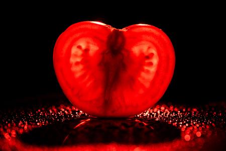 slice of fresh tomato with neon red backlit on black background 版權商用圖片
