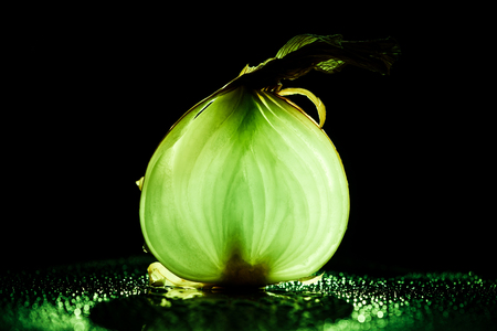 slice of raw onion with water drops and neon green back light on black background