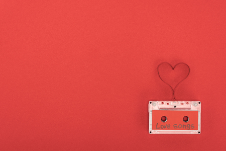 elevated view of audio cassette with lettering love songs and heart symbol made of tape isolated on red, st valentine day concept 版權商用圖片