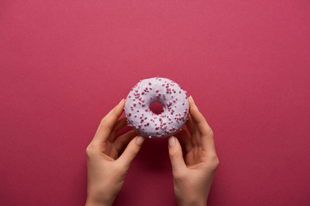 cropped view of woman holding sweet donut on ruby background