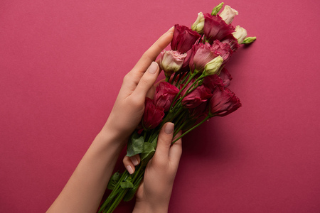 cropped view of woman holding bouquet in hands on ruby background