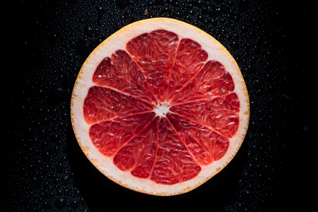 slice of grapefruit on black background with water drops Foto de archivo