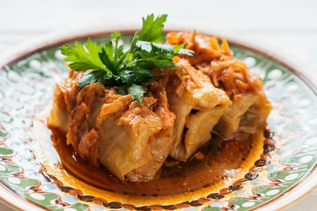 close up of traditional stuffed cabbage rolls on plate with ornament