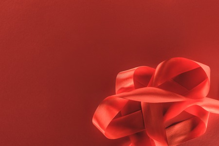 elevated view of red festive ribbon isolated on red, st valentine day concept