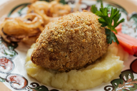 close up of tasty chicken kiev with mashed potatoes and parsley on plate with ornament