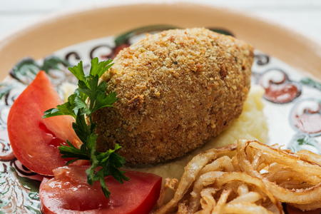close up of chicken kiev with mashed potatoes, parsley, tomatoes and fried onions on plate with ornament Standard-Bild - 116593397