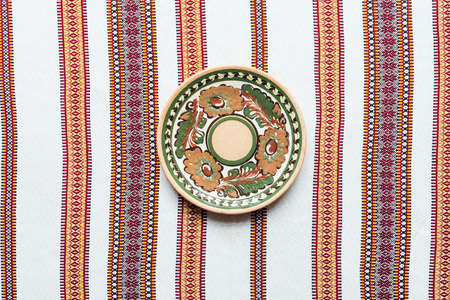 top view of plate with traditional ornament and embroidered towel on background Stock Photo