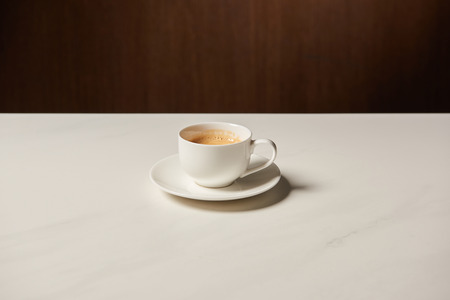 cup of hot aromatic coffee on white table