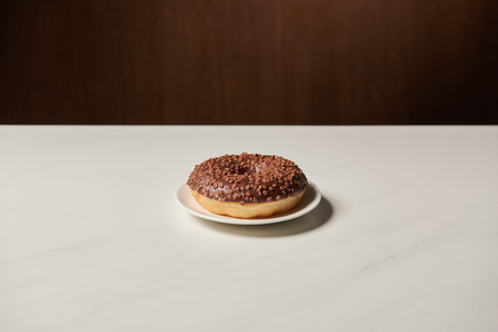 glazed chocotale doughnut with sprinkles on white table Stock Photo