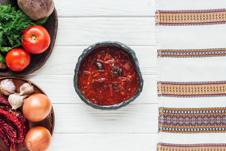 top view of traditional beetroot soup with ingredients and embroidered towel on white wooden background Standard-Bild - 116558268