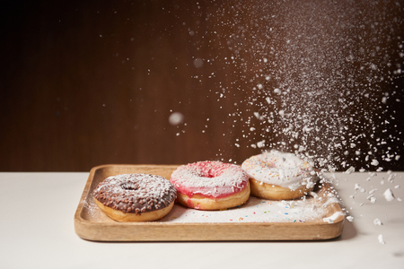 sweet donuts with sifting sugar powder on wooden cutting board Stock Photo
