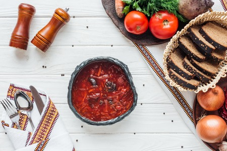 top view of delicious traditional beetroot soup with ingredients and cutlery on white wooden background Stock Photo