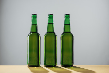 beer bottles with shadows isolated on grey, st patrick day concept