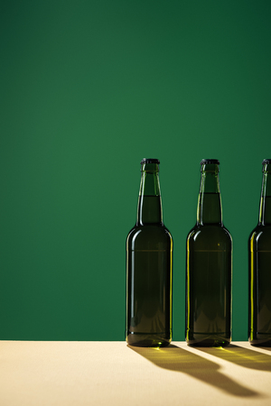 beer bottles with shadows and copy space isolated on green, st patrick day concept