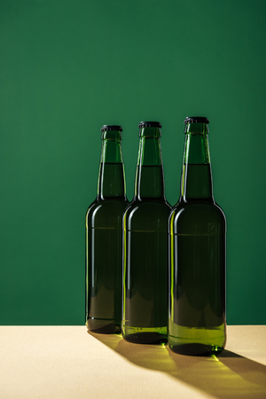 beer bottles with shadows isolated on green, st patrick day concept Stock Photo