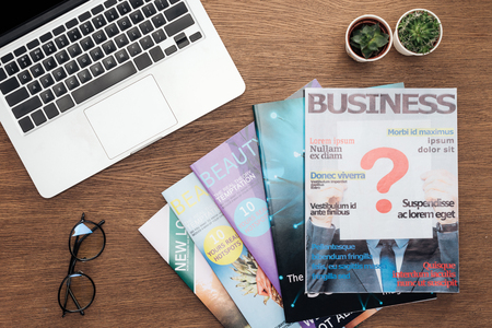 top view of laptop, business magazines, potted plants and glasses on wooden tabletop 版權商用圖片