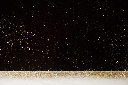 selective focus of golden sparkles falling on white table isolated on black Stock Photo