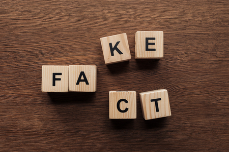 top view of on wooden cubes with words fake fact tabletop