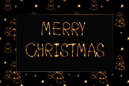 close up view of merry christmas light lettering and fir tree light signs on black background Stock Photo