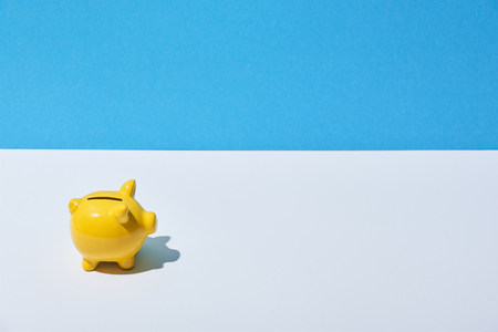 yellow piggy bank on white desk and blue background Banco de Imagens