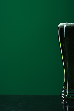 glass of beer with foam isolated on green with copy space, st patrick day concept