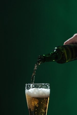 pouring beer into glass with foam isolated on green, st patrick day concept Stock Photo