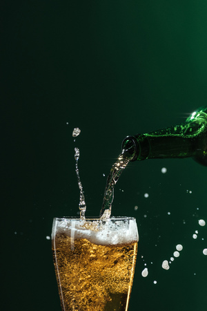 pouring beer into glass with splashes and copy space isolated on green, st patrick day concept