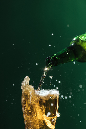 pouring beer into glass with splashes and copy space isolated on green, st patrick day concept Stock Photo - 116407805