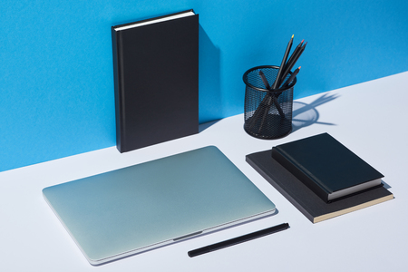 laptop, pencil holder and notebooks on white desk and blue background Stock Photo