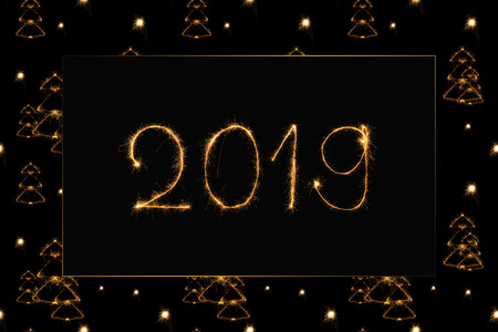2019 and fir tree light sings on black background Stock Photo