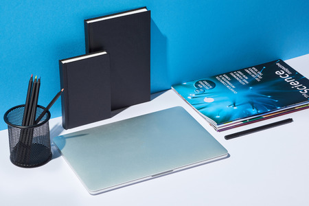 laptop, business newspaper, pencil holder and notebooks on white desk and blue background