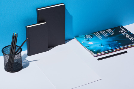paper sheet, business newspaper, pencil holder and notebooks on white desk and blue background Stock Photo