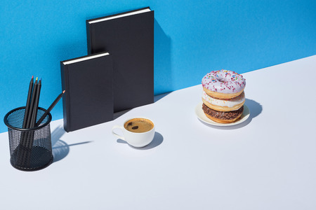 tasty donuts, coffee cup, pencil holder and notebooks on white desk and blue background Stock Photo