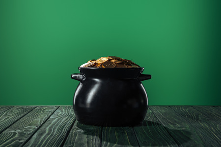 golden coins in black pot isolated on green, st patrick day concept