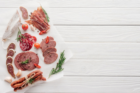 top view of arrangement of various meat snacks and rosemary on white wooden backdrop