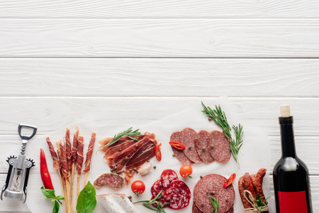 flat lay with bottle of red wine, bottle opener and meat snacks on wooden surface Stock Photo