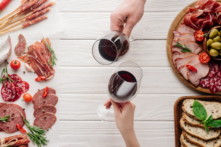 partial view of couple clinking glasses with red wine at white tabletop with meat appetizers Banco de Imagens